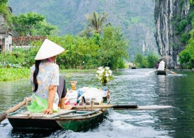 Three Caves, woman on boat groceries and fresh flowers, Ninh Bin